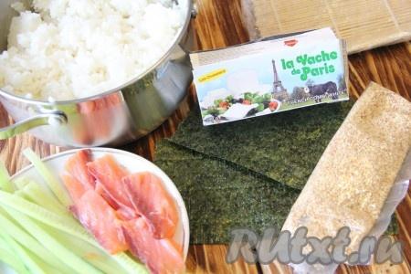 Готовый рис снять с огня и добавить рисовый уксус. Хорошо перемешать. Остудить рис до комнатной температуры. Огурец вымыть и нарезать на длинные брусочки. Рыбу нарезать на кусочки. Брынзу выложить в пакет или в кондитерский мешок с круглой насадкой.