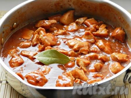 Добавить томатную пасту в сковороду, посолить, бросить лавровый лист. Перемешать и тушить еще 30-40 минут до полной готовности мяса.