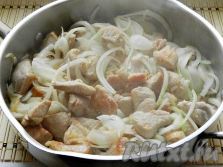Выложить лук в сковороду к мясу и обжарить, чтобы лук тоже зарумянился.