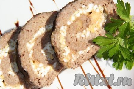 Готовыймясной рулет из фарша с яйцом слегка остудить, затем аккуратно достать из формы и нарезать на порционные кусочки. Подать аппетитное и вкусное блюдо к столу.