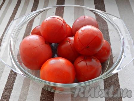 На помидорах сделать крестообразные надрезы, сложить в миску и залить кипятком на 2-3 минуты.