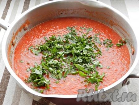 Через 15 минут добавить в томатный соус мелко порубленные листья базилика и специи. Перемешать и готовить еще 15 минут.
