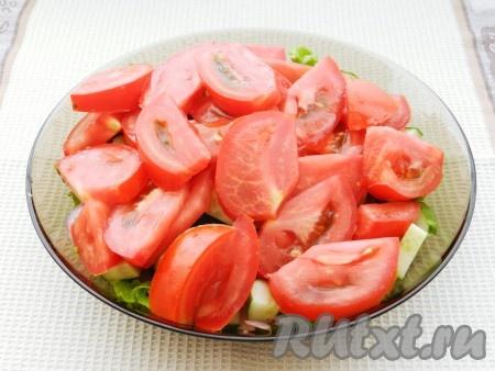 Помидоры нарезать дольками и добавить в салат. Полить половиной заправки и перемешать.