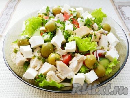 Затем добавить мелко порубленную петрушку, оливки и нарезанный кубиками сыр фета. Сверху обильно полить салат оставшейся заправкой и сразу подавать.