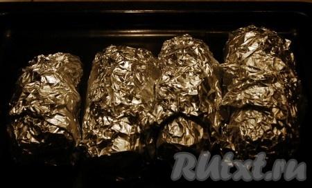 Каждый баклажан плотно заворачиваем в фольгу, укладываем на противень и отправляем в духовку запекаться при температуре 180 градусов примерно  на 1 час (пока баклажаны не станут мягкими).