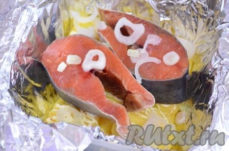 На картошку положить 1 или 2 кусочка горбуши (зависит от размера и ваших предпочтений), посыпать тонко нарезанным луком.