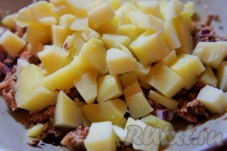 Картофель отварить в мундире. Очистить, пока картофель тёплый, и нарезать средними кубиками. Можно использовать и охлажденный вареный картофель, если вам так больше нравится, однако вкус раскроется лучше, если добавлять в салат именно тёплый картофель. Добавить картошку к рыбным консервам.