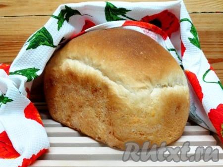 Готовый вкусный белый хлебушек вынимаем из хлебопечки и выкладываем на металлическую решётку для остывания. Прикрываем его полотенцем.