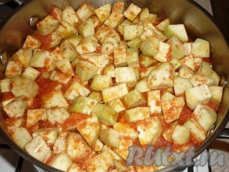 В томатную массу добавить нарезанные кусочки баклажанов и варить смесь с момента закипания пять минут. Затем добавить пропущенный через пресс чеснок, перемешать и протушить ещё 15-20 минут на среднем огне. Время приготовления зависит от баклажанов, главное их не переварить, чтобы они сохранили форму, но и не были сырыми, поэтому не забывайте периодически их пробовать на вкус.