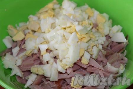 Охладить и очистить яйца, сваренные вкрутую, нарезать небольшими кубиками и добавить в салат к огурцам и куриному мясу.