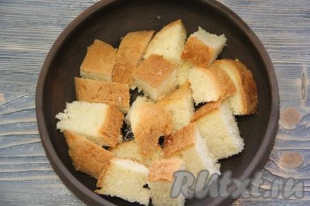 Дно жаропрочной формы слегка смазать оливковым маслом. Затем выложить кусочки хлеба. Хлеб можно нарезать на крупные квадратики или крупно поломать.