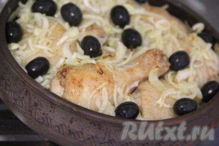 Через 20 минут достать курицу из духовки, выложить на неё лук и маслины, поставить форму обратно в духовку на 15-20 минут.