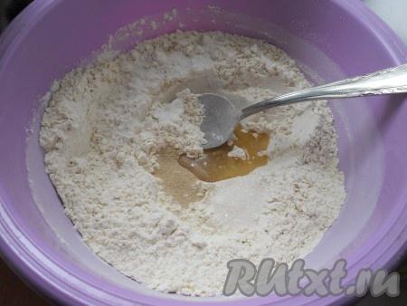 Сделать углубление, куда всыпать дрожжи, соль, сахар и растительное масло.