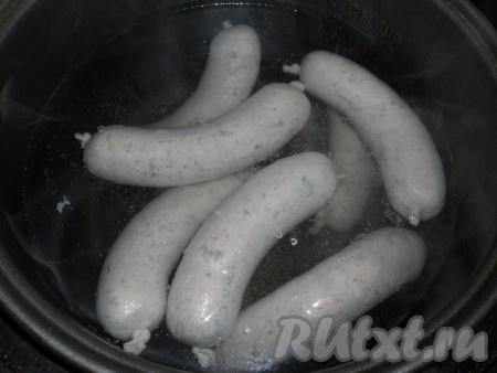 """Колбаски далее следует отварить в подсоленной воде при температуре 97-98 градусов, то есть вода не должна кипеть. Колбаски опускать в горячую воду аккуратно и варить 30 минут. Очень удобно делать это в мультиварке. Я выставляю режим """"Мультиповар"""" на 97-98 градусов, время 1 час. Через 30 минут опускаю в воду колбаски, накрываю крышкой и варю оставшееся время (30 минут)."""