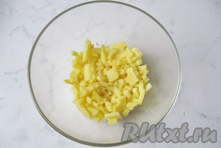 """Картофель сварить в """"мундире"""" до готовности, пока в него не будет свободно входить вилка. На это потребуется от 30 до 50 минут, в зависимости от размера картофеля и его сорта. Охладить, почистить и мелко нарезать."""