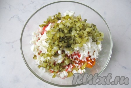 Маринованный или соленый огурец мелко нарезать, выложить в салатник.