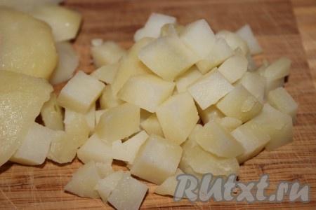 Картофель тщательно помыть при помощи щетки или губки, сложить в кастрюлю подходящего размера и залить холодной водой. Как только вода закипит, уменьшить огонь, накрыть кастрюлю крышкой и варить в течение 25-30 минут. Тут все зависит от сорта картофеля. Чтобы убедиться, что картофель готов, необходимо проткнуть его ножом или вилкой. Если картофелина легко проткнулась, значит - готова. Готовую картошку остудить, почистить и нарезать небольшими кубиками.