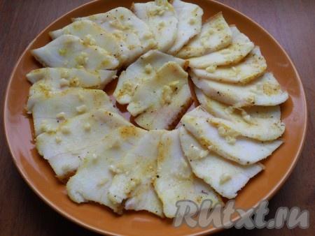 Далее с каждого кусочка сала ножом соскоблить немного соли и специй, разложить сало на тарелке и посыпать измельченным или пропущенным через пресс чесноком.