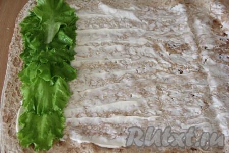 Лист лаваша смазать майонезом. Для лучшего и аккуратного формирования рулета, края лаваша лучше оставить чистыми. Затем выложить листья салата и сформировать плотную полоску.