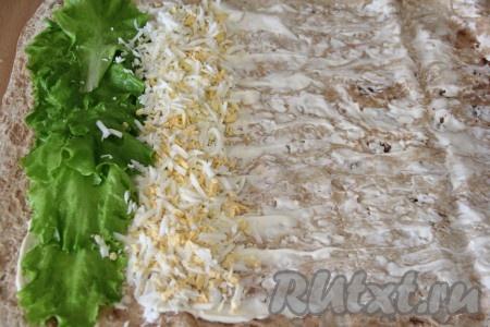 Яйца почистить и натереть на крупной тёрке. Выложить измельченные яйца рядом с листьями салата.
