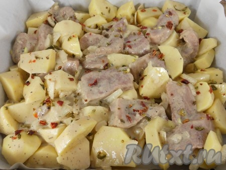Картофель очистить, нарезать крупными кусочками, смешать его со свининой. Противень или большую форму для запекания застелить пергаментом, смазать растительным маслом, выложить свинину с картошкой, посыпать сверху сушеной паприкой.