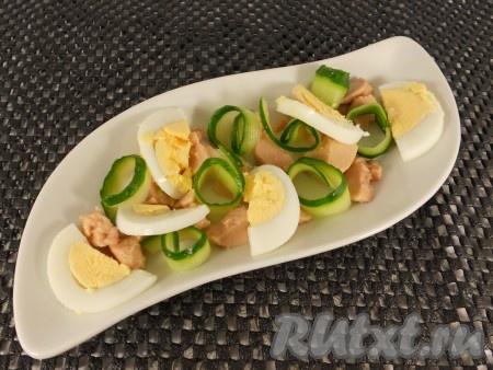 Яйцо отварить вкрутую, остудить и очистить. Между кусочками печени трески поместить огурцы, свернутые в рулетики, и яйцо, нарезанное небольшими дольками.