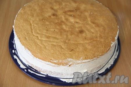 Поверх крема выложить второй корж и слегка прижать. Смазать кремом бока коржей.