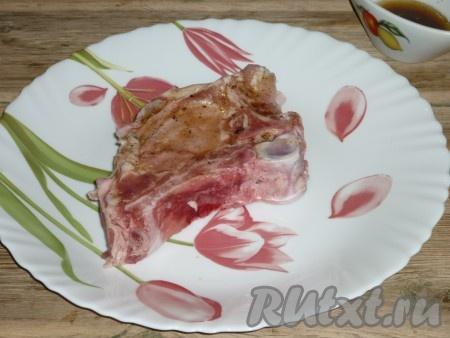 Свиные котлеты на кости промыть под проточной водой и обсушить бумажным полотенцем. Маринадом обмазать мясо со всех сторон. Оставить на 1 час, чтобы замариновалось и хорошо пропитались специями и растительным маслом.