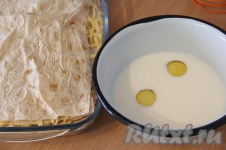 Таким образом сделать несколько слоёв: лаваш, сыр, лаваш, сыр, верхним слоем должен остаться лаваш. Молоко вылить в глубокую миску и добавить яйца.