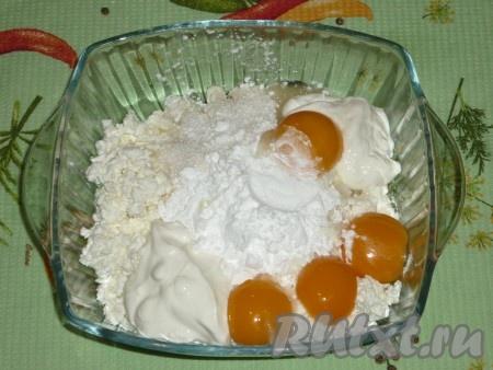Яйца разделить на желтки и белки. Соединить творог с крахмалом, яичными желтками, сметаной и 5 столовыми ложками сахара.