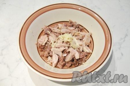 Из мяса удалить кости, шкурку, жир и сухожилия. Должна остаться одна мякоть. Мелко нарезать мясо курицы и говядины. Разложить по глубоким тарелкам. Почистить, помыть и измельчить любым способом чеснок. Добавить в каждую тарелку.