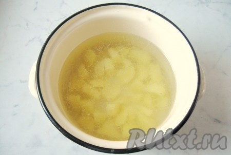 Готовый бульон процедить и налить в кастрюлю 1,5 литра. Картофель почистить, помыть и нарезать кубиками. Выложить картофель в кастрюлю с бульоном. Накрыть кастрюлю крышкой и поставить на плиту. Начать варить рассольник.