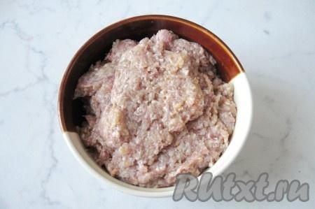 Пока варится бульон, приготовить фарш для фрикаделек. Одну луковицу и два зубчика чеснока почистить и измельчить любым способом. Мясной фарш (у меня говяжий) выложить в миску, добавить в него яйцо, измельченный лук и чеснок. Посолить и поперчить по вкусу. Фарш тщательно перемешать. Не лишним будет взбить его блендером для придания большей однородности.