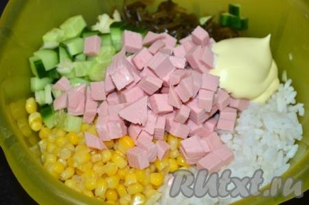 В миску с рисом, кукурузой и морской капустой добавить колбасу, огурец и чеснок, посолить, поперчить по желанию, заправить салат майонезом или сметаной.