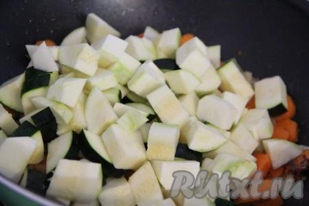 Кабачок и баклажан вымыть и срезать хвостики. Если у кабачка жёсткая шкурка, лучше её снять. Нарезать кабачок и баклажан средними кубиками и добавить в сковороду. Всё тщательно перемешать и жарить в течение 10 минут при помешивании.