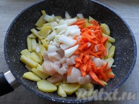 Разогреть растительное масло в сковороде, добавить туда нарезанный соломкой или кубиками картофель. Обжарить картошку на среднем огне, периодически помешивая, до небольшой румяной корочки (минут 5-7). Далее добавить к картофелю курицу, лук и морковь. Перемешать и обжаривать все вместе еще 7-10 минут на небольшом огне, периодически перемешивая. Картофель в итоге должен быть почти готов.