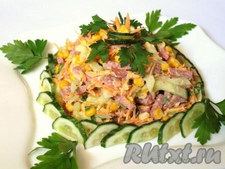 Выложить на тарелку и украсить, как подскажет фантазия, очень вкусный салат с копчёной колбасой, кукурузой и огурцами.