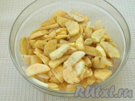 Картошку нарезать ломтиками, посыпать солью, приправой для картофеля, влить растительное масло и хорошо перемешать.