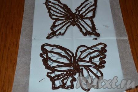 Тем временем можно заняться созданием украшений для нашего торта – шоколадных бабочек. Для этого нужно предусмотрительно позаботиться о заготовках-трафаретах с изображением бабочек и листе пергамента. Мы накладываем пергамент на лист с изображением бабочек, сгибаем пополам (чтобы линия сгиба проходила по центру бабочек) и через прозрачный пергамент нам замечательно видно изображение – вот его контур мы и будем повторять шоколадом, растопленным на паровой бане.