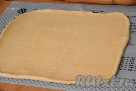 С помощью скалки раскатать тесто в прямоугольный пласт.